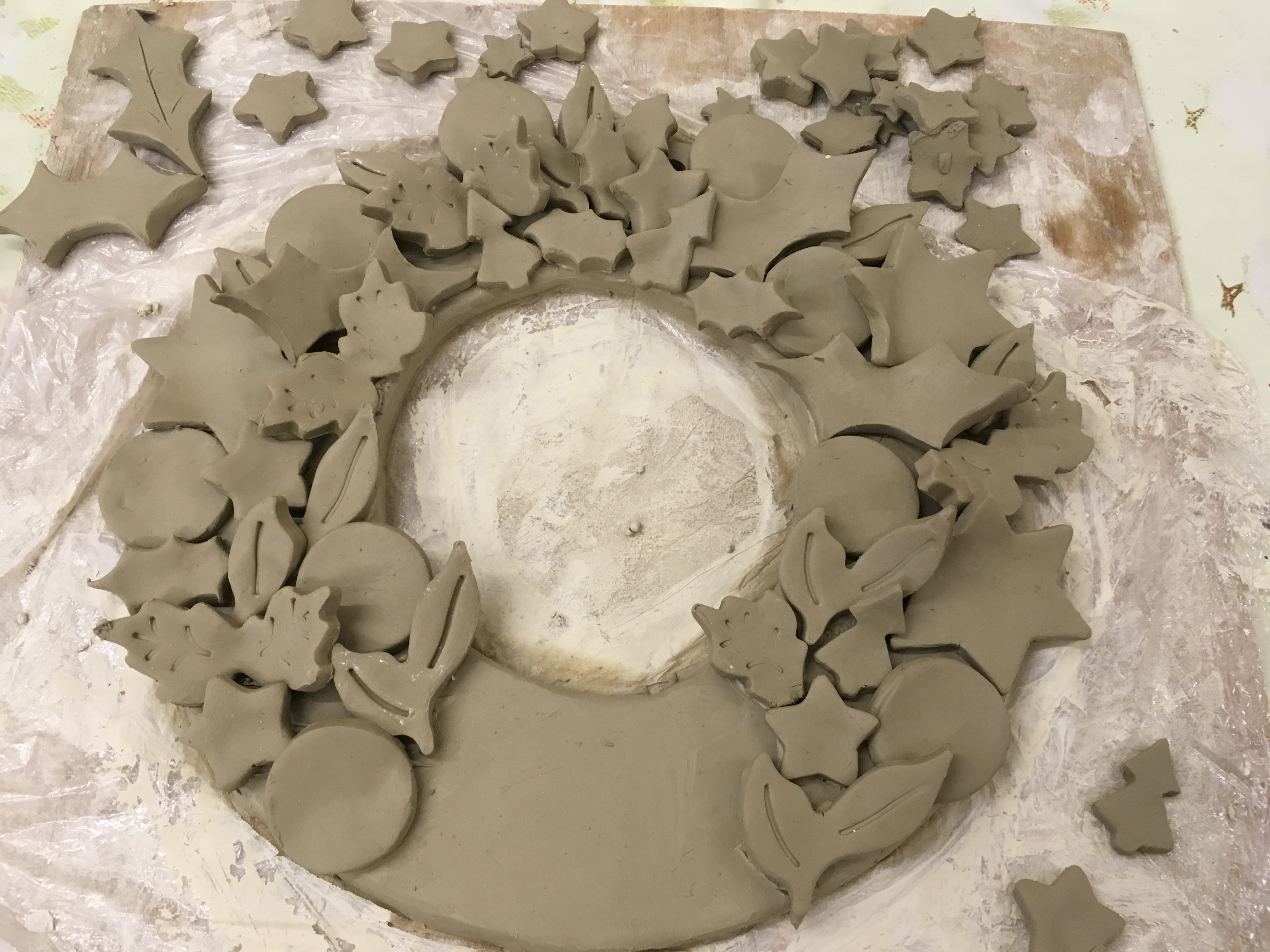 Clay work making a ceramic Christmas wreath